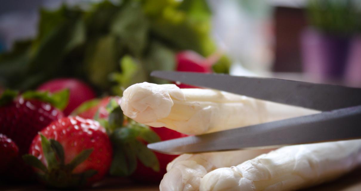 Bild von Spargel und Erdbeeren, dem Spargel wird mit einer Schere der Kopf abgeschnitten, soll die Ausbeutung in der Spargelproduktion symbolisieren