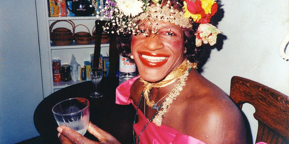 Bild von Marsha P. Johnson mit Blumen in den Haaren, lächelt in die Kamera