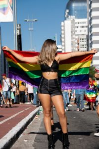 woman-in-black-top-and-shorts-holding-rainbow-flag-2577848