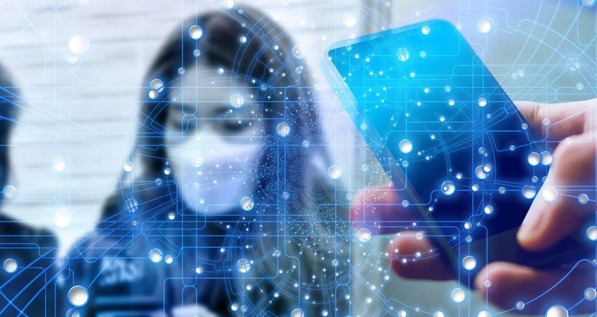 Ein Symbolbild zum Coronavirus, stellt eine Frauen mit Mundschutz und ein Handy dar, auf dem man Informationen erhalten kann